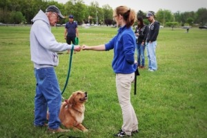 Emily training owner and his dog Stephanie for obedience training outdoors